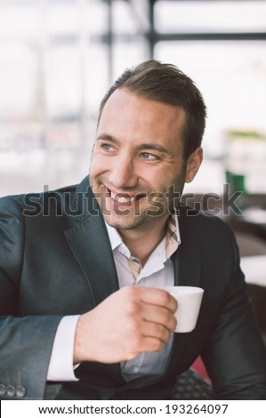 Handsome smiling man drinking espresso in cafe  - stock photo