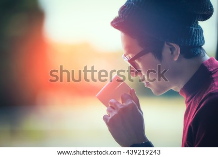 Handsome smiling man guy in  looking through the window with a cup of morning coffee concept waiting dreaming. - stock photo