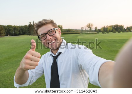 Handsome smiling man making selfies and showing thumb-up isolated on green environment. Man in glasses smiling for the camera. - stock photo