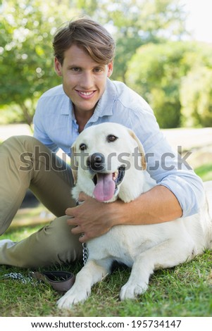 Handsome smiling man with his labrador sitting in the park on a sunny day - stock photo