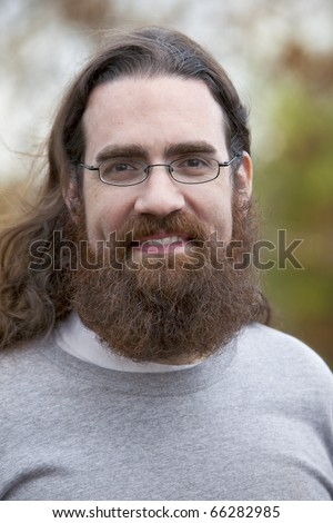 Handsome smiling man with long hair, beard and glasses outdoors in Autumn season - stock photo