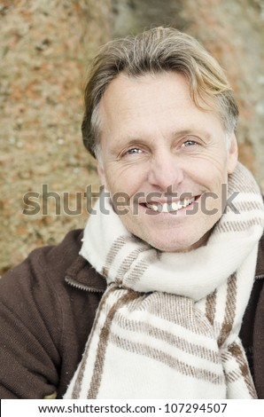 handsome smiling mature blond man wearing a brown pullover and scarf. - stock photo