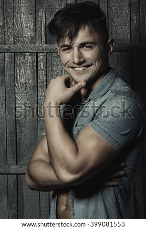 Handsome smiling sexy sensual muscular young macho man with bare torso and stylish hair in jeans shirt indoor on wooden background, vertical picture - stock photo