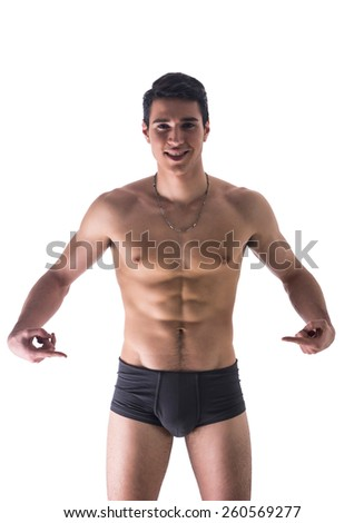 Handsome, smiling, shirtless young man in underwear pointing fingers at empty blank space for copy, isolated on white - stock photo
