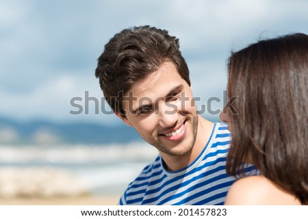 Handsome smiling young man listening to his wife speaking as they enjoy a summer day at the beach together, with copyspace - stock photo
