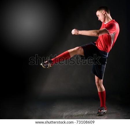handsome soccer player kicks ball on black background - stock photo