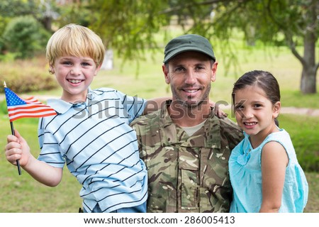 Handsome soldier reunited with family on a sunny day - stock photo