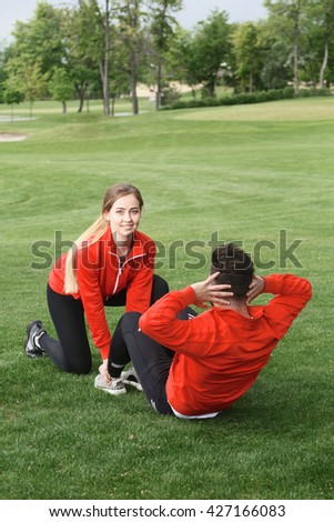 Handsome sport man doing abdominal cruches in green park or forest while smiling lady holding his hands. - stock photo
