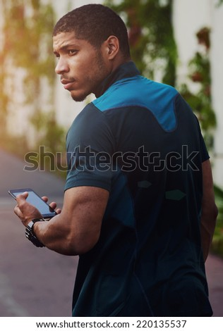 Handsome sportsman holding mobile phone and looking away, muscular build dark skin runner resting after run using his mobile phone, attractive muscular runner taking break,  using technology concept - stock photo