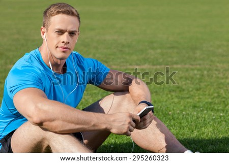 Handsome sportsman is listening to music and looking at the camera with pleasure. He is sitting on grass. The man has headphones in his ears and telephone in arms. There is copy space in right side - stock photo