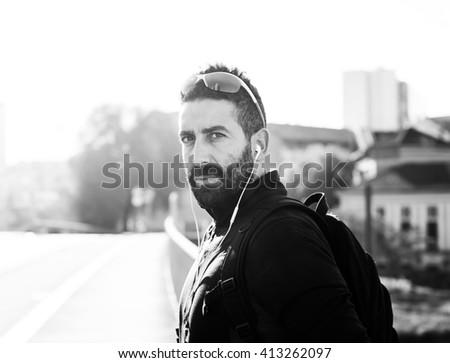 Handsome sportsman portrait in the city wearing earphones monochrome - stock photo