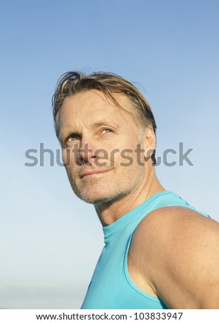 Handsome sportsman with stubble wearing a blue tank top. - stock photo