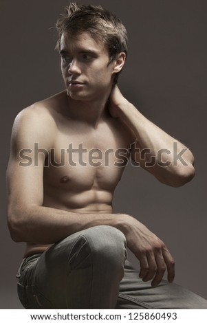 Handsome sporty male model with great body build, tattoo on his left arm, his torso naked, wearing   jeans,  sitting on the floor in studio. - stock photo