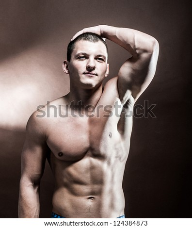 Handsome strong athletic man on black background - stock photo