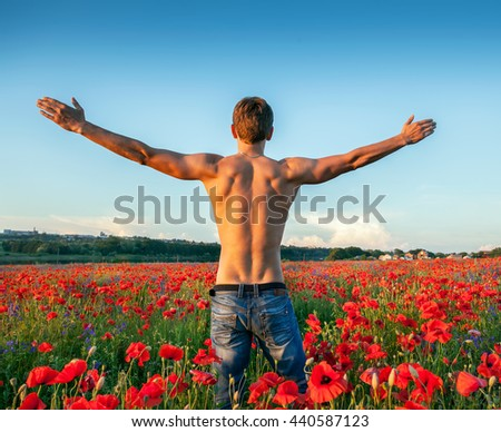 Handsome strong sexy man on a beautiful field - stock photo