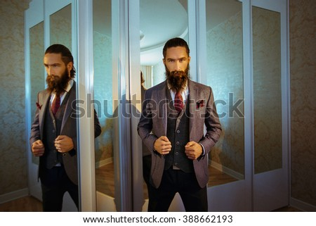 Handsome strong stylish bearded groom posing near mirror - stock photo