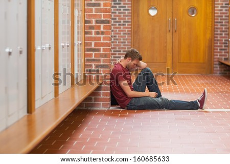 Handsome student in pain having a headache in school - stock photo