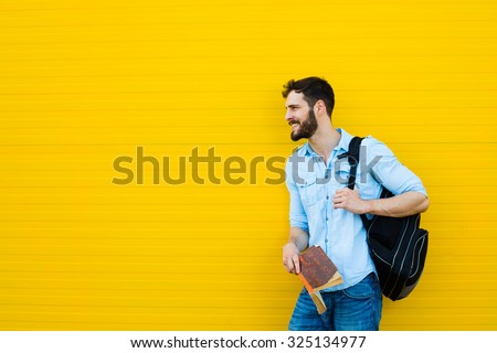 handsome student with backpack standing outside on yellow background - stock photo