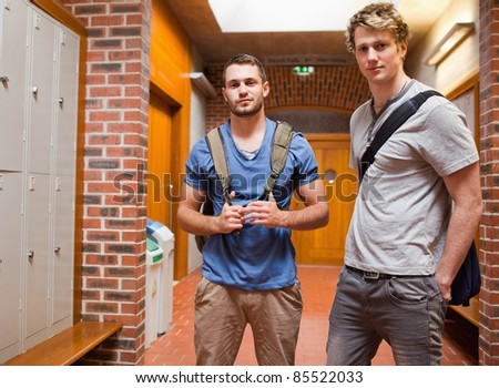 Handsome students posing in a corridor - stock photo