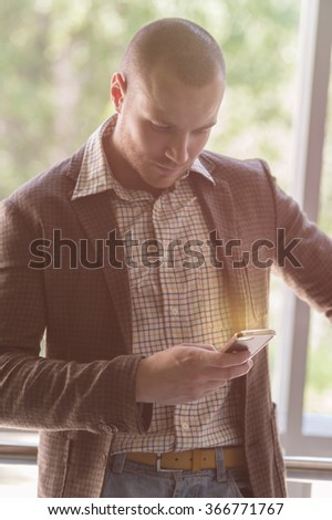Handsome stylish businessman texting on the phone in office - stock photo