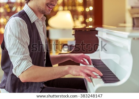 Handsome stylish man in classical vest smiling while playing a piano in a musical shop, cropped - stock photo