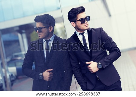 handsome stylish man in elegant black suit and sunglasses in the street - stock photo