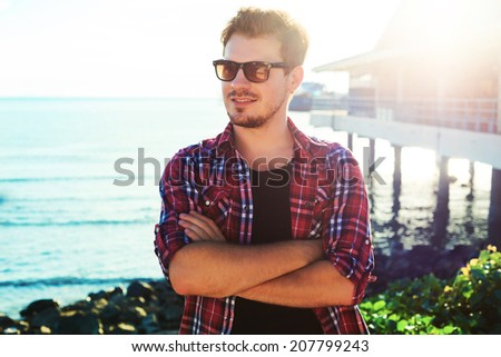 Handsome stylish man in hipster plaid shirt and sunglasses posing near sea side at sunshine, enjoying beautiful view and relax near ocean. - stock photo