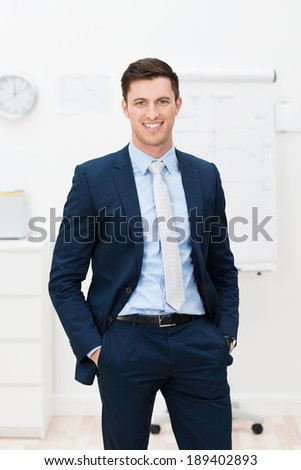 Handsome stylish young businessman standing smiling confidently at the camera with his hands in his pockets and jacket unbuttoned - stock photo