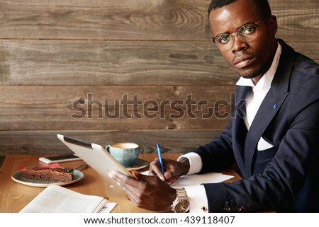 Handsome successful African entrepreneur wearing formal suit and spectacles, signing papers while using tablet. Portrait of dark-skinned man holding digital device for distant work at a coffee shop - stock photo