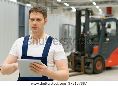 Handsome supervisor with tablet pc at the warehouse. - stock photo