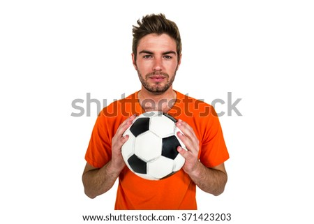 Handsome supporter holding football ball on white screen - stock photo