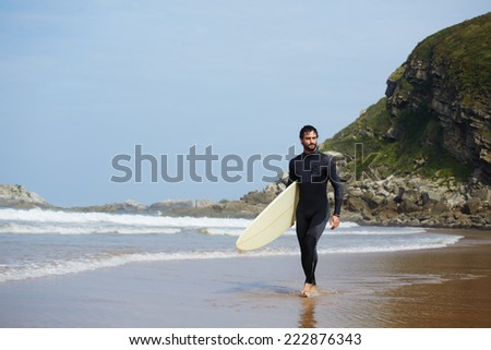 Handsome surfer walks carrying surfboard with big mountain rock on background, perfect sunny day for surfing on big waves, young handsome surfer man walking with surfboard on the beach - stock photo