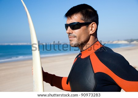 Handsome surfer wearing sunglasses and a wetsuit holding his surf board overlooking the ocean. - stock photo