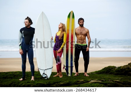Handsome surfers guys and blond hair girl standing on the beach with beautiful ocean waves on background holding surfboards with copy space area for advertising - stock photo