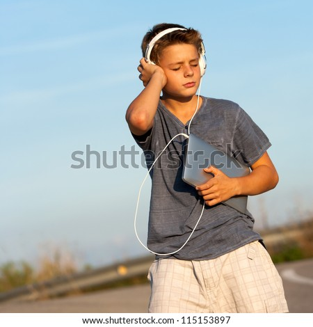 Handsome teen boy enjoying music on tablet outdoors. - stock photo
