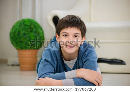 Handsome teen boy lying on floor at home - stock photo