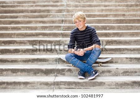 handsome teen boy sitting on skateboard - stock photo