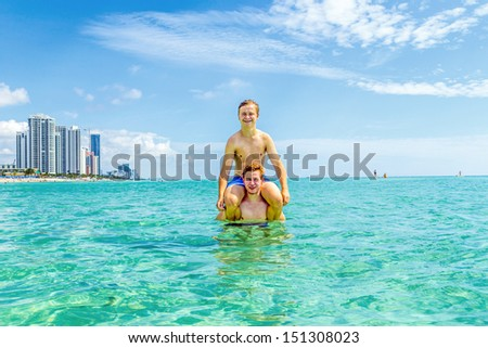 handsome teen have fun playing piggyback in the ocean - stock photo