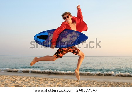Handsome teen jumping in the beach with skimming board - stock photo