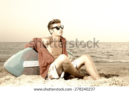 Handsome teen posing in the beach with skimming board - stock photo