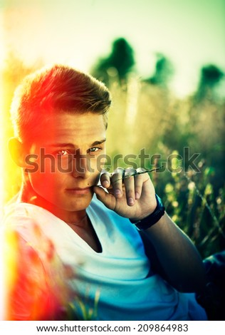 Handsome teenage guy lying on the field. Young man enjoying nature outdoors. Looking an camera and smiling. - stock photo