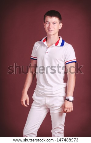 Handsome teenager in casual wear posing in studio. Stylish smiling male model. Happy boy in fashion T-shirt waiting for girlfriend. thoughtful man wearing stylish watch - stock photo