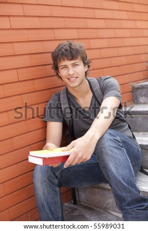 handsome teenager next to a red brick wall (selective focus) - stock photo