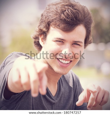 Handsome teenager pointing to you  - stock photo
