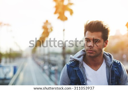 Handsome thoughtful man looking away while standing against road and sky background with copy space area for your text message or content, attractive male posing for camera on the street outdoors - stock photo