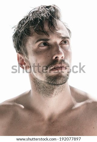 Handsome thoughtful unshaven shirtless young man with a goatee beard standing looking upwards with a frown and a serious meditative expression, isolated on white - stock photo