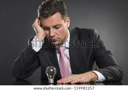 Handsome tired and stressed businessman resting at his desk and looking at light bulb, in lack of ideas. - stock photo