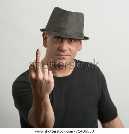 Handsome tough man giving middle finger, DOF focus on hand - stock photo