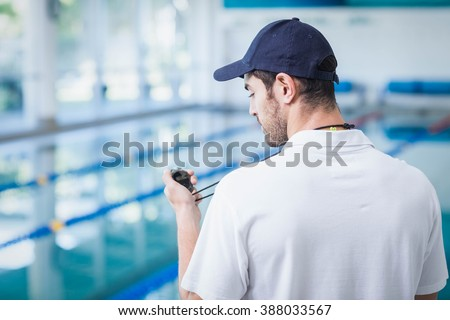 Handsome trainer looking at stopwatch at the pool - stock photo