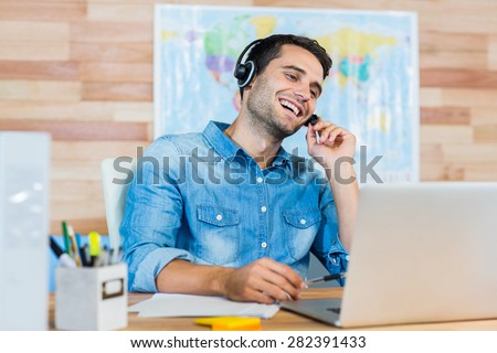 Handsome travel agent speaking with customer in the office - stock photo